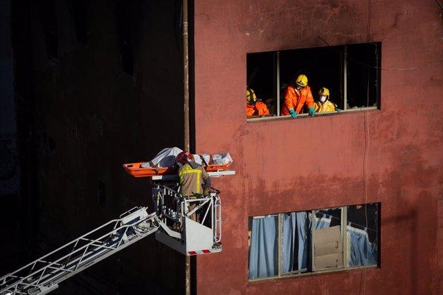 Els Bombers de la Generalitat han retirat de l'interior de la nau dos dels tres cossos sense vida de les víctimes de l'incendi. Badalona (Barcelona), 10 de desembre del 2020.