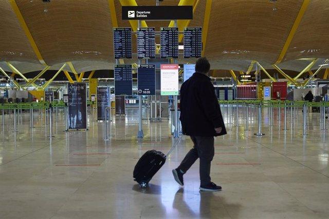 Un pasajero camina por la terminal T4 del Aeropuerto Adolfo Suárez Madrid-Barajas durante el primer día de cierre perimetral por el puente de la Constitución en Madrid (España), a 4 de diciembre de 2020.