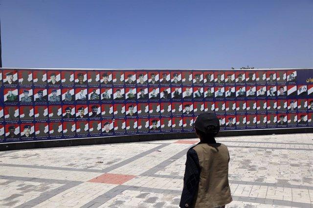 Imagen de archivo de un niño frente a fotos de víctimas del terrorismo en Yemen.