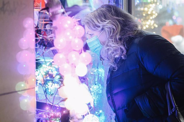 Una mujer con mascarilla mirando las lueces navideñas en una tienda