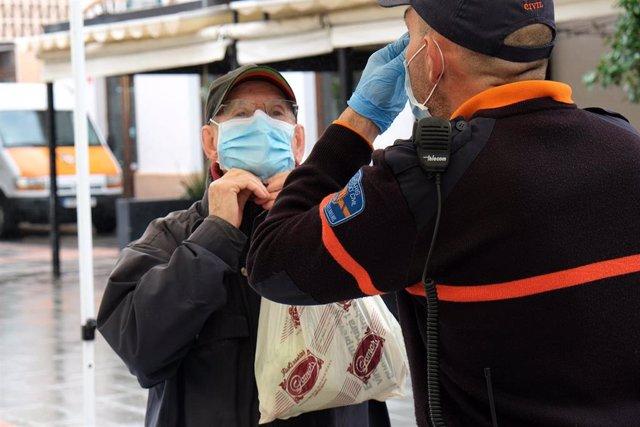 Un hombre recibe las indicaciones de cómo colocarse la mascarilla por parte de un agente local de Palma.
