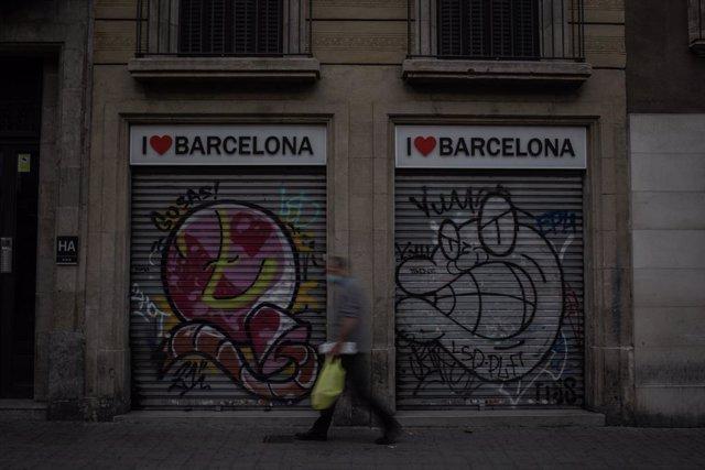 Un home camina al costat de dues botigues turístiques. Barcelona, Catalunya (Espanya), 16 de novembre del 2020.