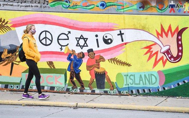 Una estudiante con mascarilla pasea frente a un mural en Rock Island, en Estados Unidos