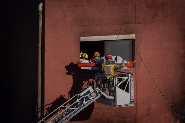 Bombers retirin el cadàver d'una dels personis mortes en l'incendi d'ahir en la nau okupada del barri de Gorg, a Badalona, Barcelona, Catalunya (Espanya), 10 de desembre del 2020.