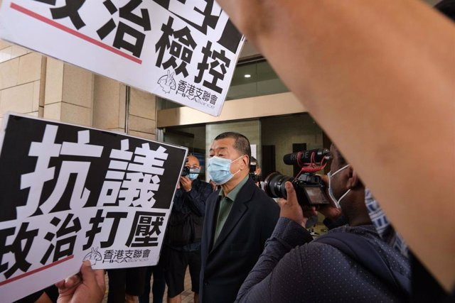 03 November 2020, China, Hong kong: Activists and supporters hold placards as pro-democracy media tycoon Jimmy Lai arrives at West Kowloon Magistrates' Court where he and 26 Hong Kong pro-democracy activists, are being accused of taking part in an illegal
