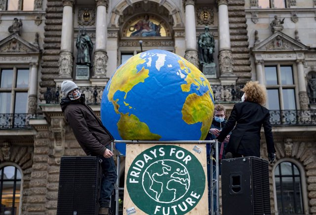 "11 December 2020, Hamburg: Activists of ""Fridays for Future"" carry a ballon in the shape of the earth while building a so-called ""Gallery of Failure"" on the Hamburg City Hall Market on the nationwide day of action to commemorate the 1.5-degree target for"
