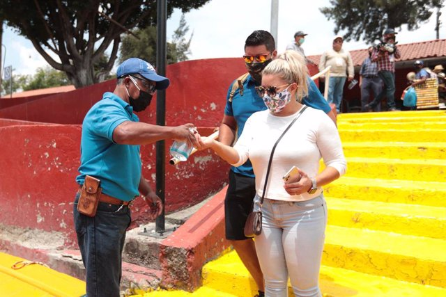 21 August 2020, Mexico, Mexico City: Aworker disinfects the hands of a visitor before boarding one of the Trajineras, the colorful boats of Xochimilco. The popular tourist spot of Xochimilco canals reopened on Saturday, after months of closure due to the