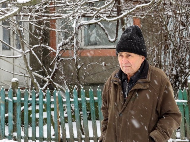 Old man during a snowfall. Cold weather, first snow