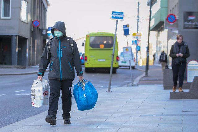 13 March 2020, Norway, Oslo: A man wearing a surgical mask walks through the streets of Oslo with shopping bags amid the coronavirus outbreak. Photo: Hkon Mosvold Larsen/scanpix/dpa