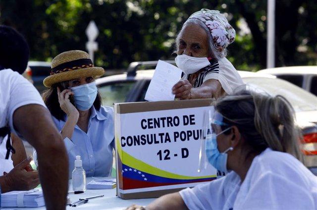 Una mujer mete en la urna su papeleta en la consulta popular organizada por la oposición en Venezuela.
