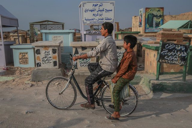 12 November 2020, Iraq, Najaf: Children ride a bicycle through Wadi al-Salam (Valley of Peace)cemetery in the Shiite holy city of Najaf. The ancient Islamic cemetery, established in 7th century near the shrine of Imam Ali, is  considered the world's larg