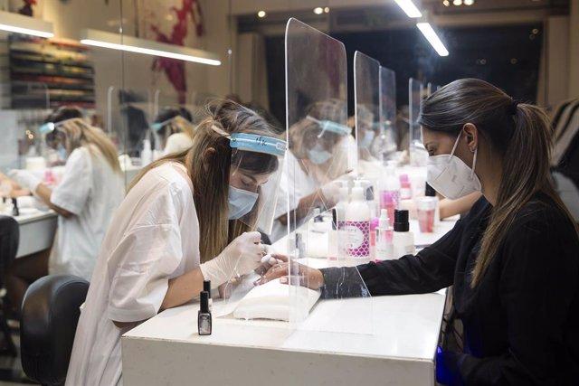 Mujeres con mascarilla en un taller de manicura en Tel Aviv, Israel