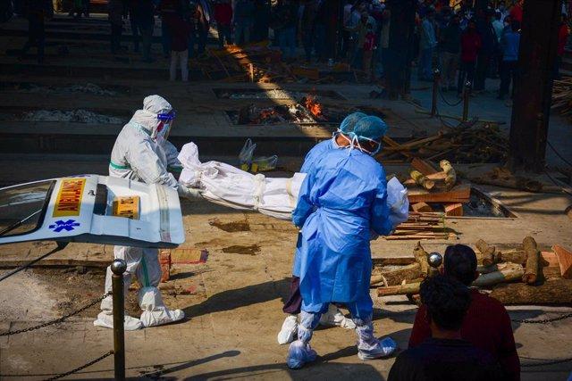 Trabajadores sanitarios trasladan el cadáver de una víctima del coronavirus en Nueva Delhi