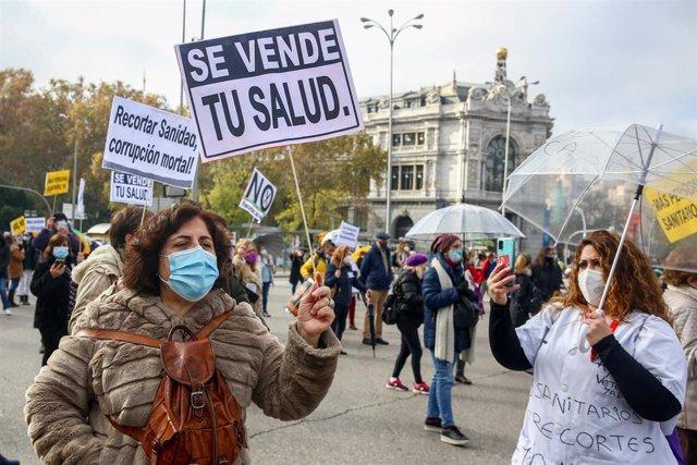 """Una mujer sostiene una pancarta donde se lee """"Se vende tu salud"""" durante una manifestación de la Marea Blanca en Madrid (España), a 29 de noviembre de 2020."""