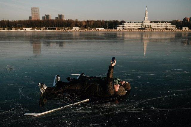 Dos ciudadanos se hacen un selfie sobre el hielo del canal Grebnoy en Moscú