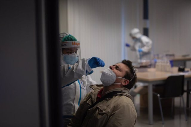 Un hombre recibe una prueba PCR en un dispositivo de cribados masivos.