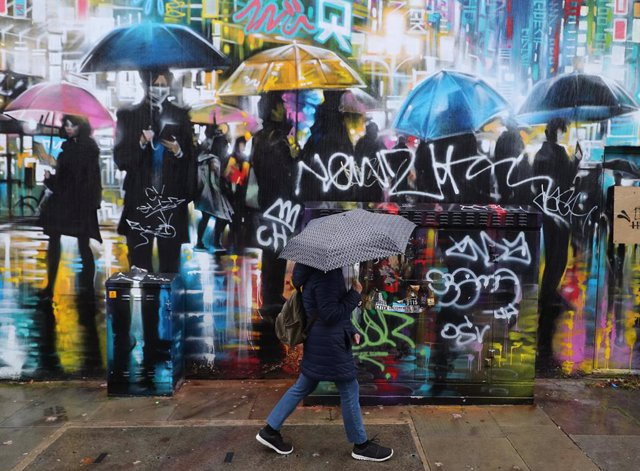 21 October 2020, England, London: A woman with an umbrella walks past a street mural. Photo: Yui Mok/PA Wire/dpa