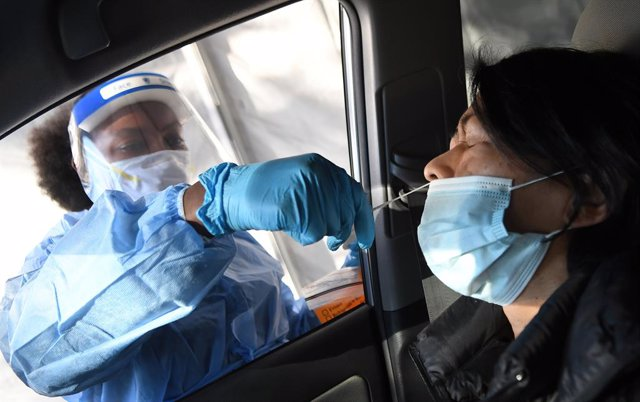 08 December 2020, US, Orlando: A medical worker takes a nasal swab from a woman at a rapid coronavirus (COVID-19) test site. Photo: Paul Hennessy/SOPA Images via ZUMA Wire/dpa