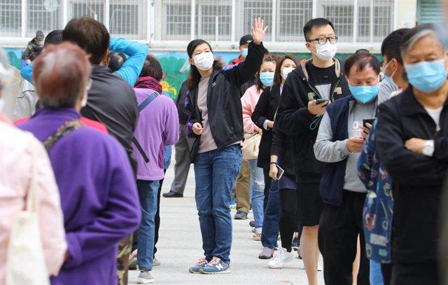 Un grupo de residentes de uno de los edificios en los que se ha localizado un último brote de la COVID-19 en Hong Kong hace turno para someterse a una prueba de coronavirus.
