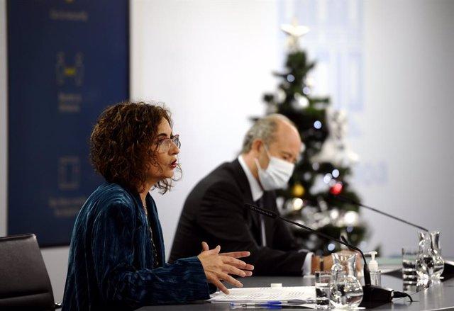 La ministra portavoz y de Hacienda, María Jesús Montero (i), y el ministro de Justicia, Juan Carlos Campo (d), comparecen en rueda de prensa posterior al Consejo de Ministros celebrado en Moncloa, en Madrid (España), a 15 de diciembre de 2020.
