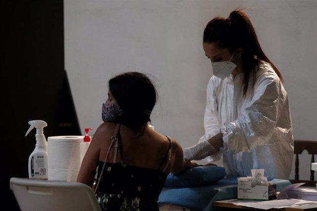 Una sanitaria saca sangre a una mujer