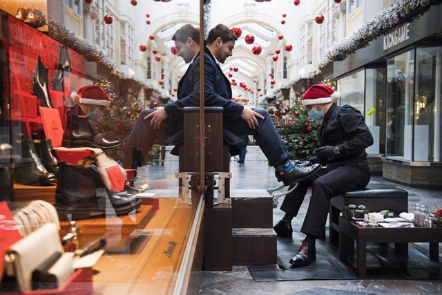 15 December 2020, England, London: A man has his shoes shined at Burlington Arcade in London before the city moves into the highest tier of coronavirus restrictions from Wednesday as a result of soaring case rates. Photo: Kirsty O'connor/PA Wire/dpa