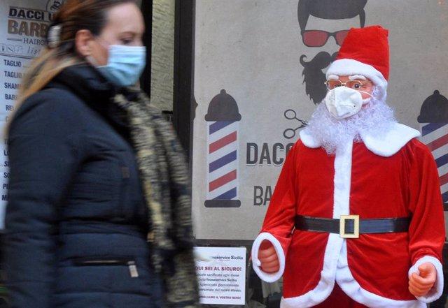 Una mujer con mascarilla pasando junto a un Papá Noel con mascarilla en Palermo, Sicilia, Italia