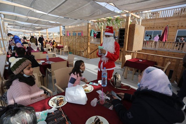 14 December 2020, Palestinian Territories, Gaza: A Palestinian waiter dressed as Santa Claus serves customers in a cafe on the beach of Gaza City as part of the Christmas celebration. Photo: Ashraf Amra/APA Images via ZUMA Wire/dpa