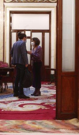 El vicepresidente del Gobierno, Pablo Iglesias y la portavoz del Gobierno y ministra de Hacienda, María Jesús Montero mantienen  una conversación durante una sesión de control al Gobierno, en Madrid (España), a 16 de diciembre de 2020. Durante el pleno, e
