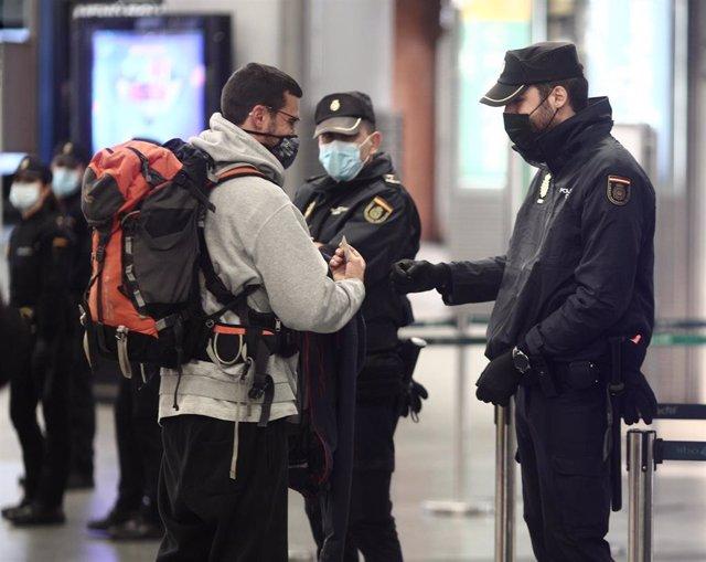 Agentes la Policía Nacional realizan controles de movilidad en la estación de AVE Puerta de Atocha durante el primer día de cierre perimetral por el puente de la Constitución en Madrid (España), a 4 de diciembre de 2020.