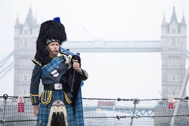 HANDOUT - 15 August 2020, England, London: Pipe Sergeant Neil Esslemont of RAF Halton Pipes & Drums plays in front of the Tower Bridge on the 75th anniversary of the Victory over Japan Day. Photo: Po Phot Dave Jenkins/Mod via PA Media/dpa - ATTENTION: edi