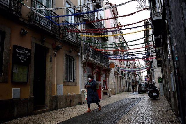 Una mujer con mascarilla pasea por Lisboa
