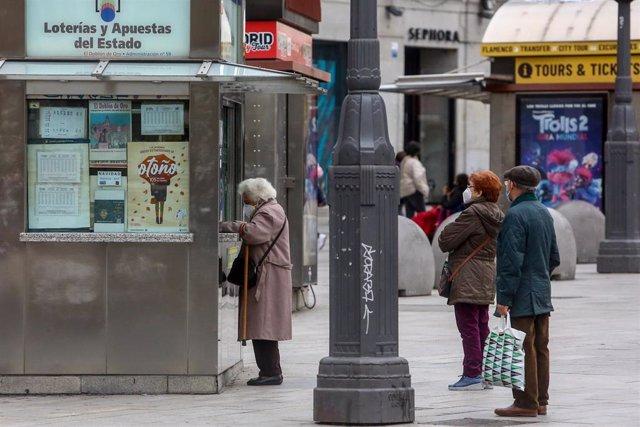 Varias personas hacen cola en las inmediaciones de una administración de la Puerta del Sol donde venden boletos para el Sorteo Extraordinario de la Lotería de Navidad 2020, en Madrid (España), a 4 de noviembre de 2020. A un mes y medio del tradicional sor