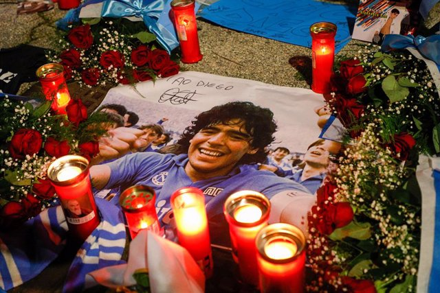 26 November 2020, Italy, Naples: Flowers and candles are laid at a makeshift memorial dedicated to the memory of late Argentinian football legend Diego Maradona
