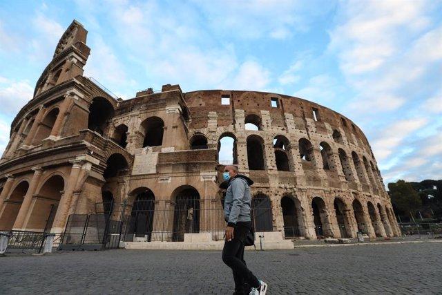 Un home amb mascareta passeja davant del Coliseu.