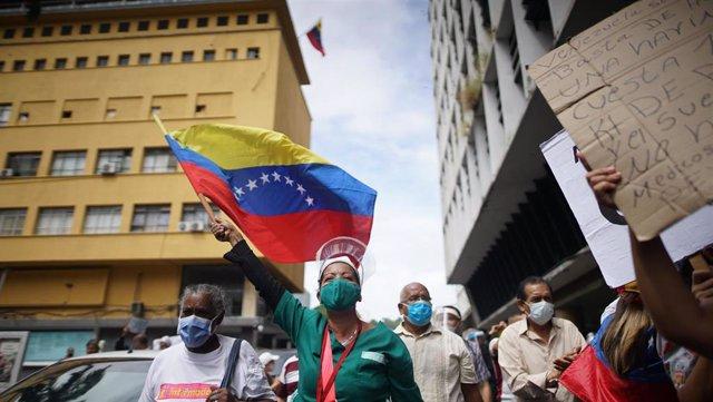 Una trabajadora del sector sanitario ondea una bandera de Venezuela durante una protesta para pedir mejores condiciones a los sanitarios durante la pandemia del coronavirus.