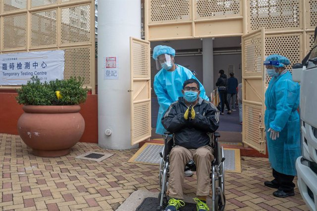 16 December 2020, China, Hong Kong: A health worker in Personal Protective Equipment assists a disabled man in a wheelchair at a makeshift coronavirus (COVID-19) testing centre near a public housing estate. Photo: Geovien So/SOPA Images via ZUMA Wire/dpa