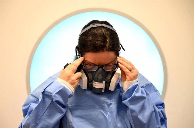Una médico poniéndose el Equipo de Protección Personal en un hospital de Cambridge