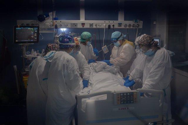 Diversos treballadors sanitaris protegits atenen un pacient a la unitat de vigilància intensiva (Arxiu)