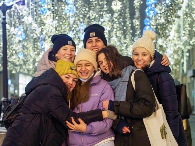 Varias personas posan sin mascarilla ante las luces navideñas en Moscú