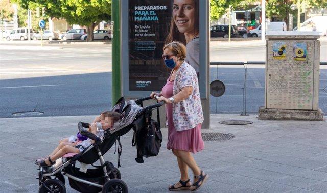Una señora con mascarillas pasea a dos niños ante un cartel publicitario en el primer día  de uso obligatorio de mascarillas en Sevilla a 15 de julio del 2020