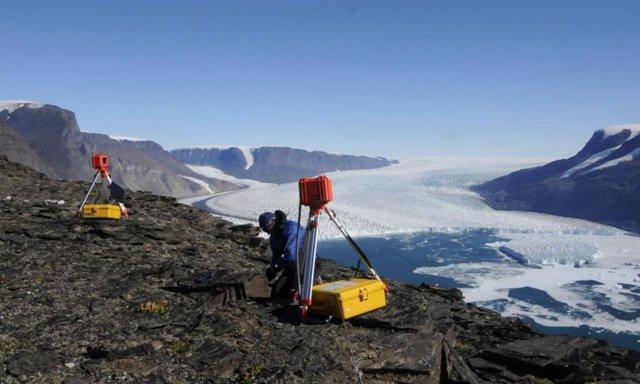 Un investigador (Leigh Stearns, Universidad de Kansas) ajusta una cámara de lapso de tiempo que monitorea el frente de Kangilliup Sermia (también conocido como Rink Isbrae), un glaciar de salida en Groenlandia.