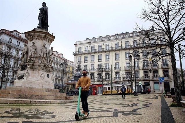 Un joven con mascarilla pasea en un patinete por Lisboa