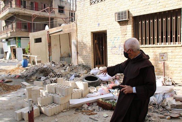 El padre Raymond Abdo entre los escombros en Beirut, provocados por la explosión de agosto de 2020.