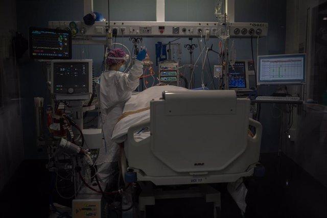 Trabajadores sanitarios protegidos atienden a un paciente en la Unidad de Cuidados Intensivos –UCI- del Hospital del Mar, en Barcelona, Catalunya (España), a 19 de noviembre de 2020.