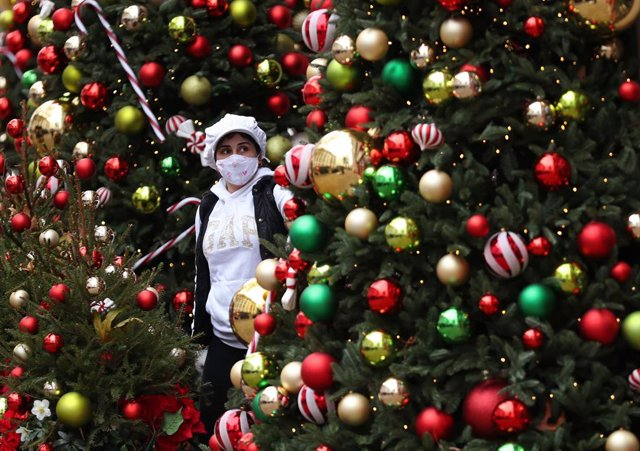 16 December 2020, England, London: A woman stands amongst a festive display outside a restaurant at Kensington High Street in London which has been placed in the highest level of coronavirus restrictions due to rising case numbers. Photo: Yui Mok/PA Wire/