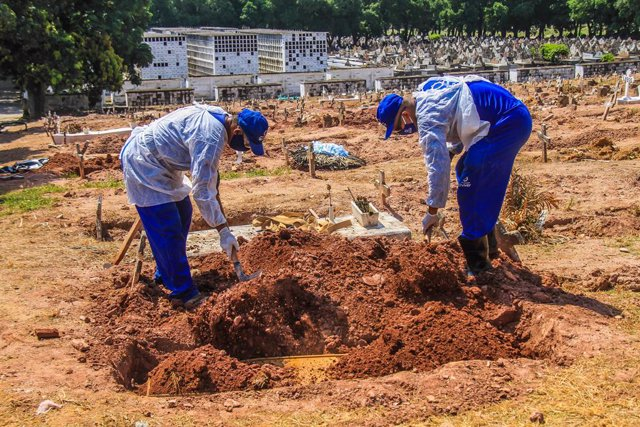 16 December 2020, Brazil, Rio de Janeiro: Cemetery workers in protective suits bury the body of a man who died from the coronavirus (COVID-19) at Sao Francisco Xavier cemetery. Photo: Ellan Lustosa/ZUMA Wire/dpa