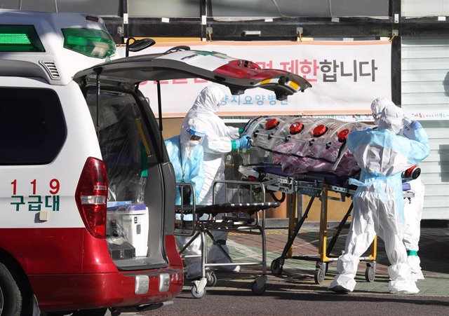 17 December 2020, South Korea, Ulsan: Medical workers clad in protective gear carry a patient infected with the coronavirus (COVID-19) onto an ambulance at an elderly care facility Photo: -/YNA/dpa