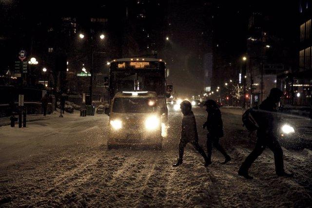 Varias personas cruzan la calle en medio de la nevada en Nueva York