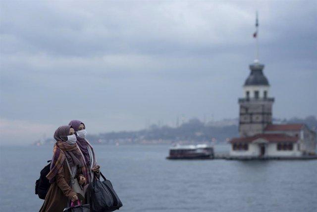 Dos mujeres con mascarilla pasean ante la Torre de la Doncella en Estambul